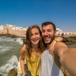 Beautiful tourist couple smiling and taking photo selfie with Cityscape of Essaouira, a UNESCO world heritage site in Morocco