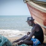 Unidentified Angolan fisherman sitting in front of red fishing boat at beach fixing nets