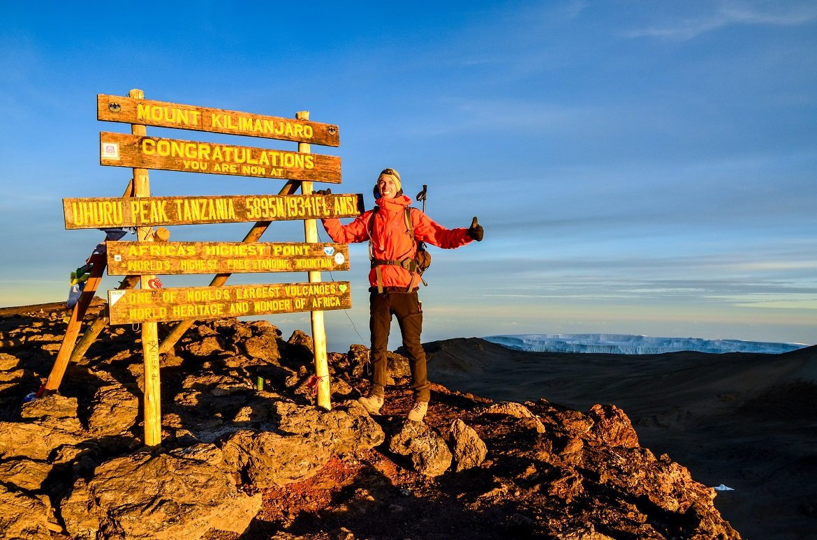 Kilimanjaro, Tanzania - March 11, 2015 A hiker standing on Uhuru Peak, the summit of Kibo and highest mountain in Africa, Mount Kilimanjaro at 5895m amsl. Summit sign and glacier in the background