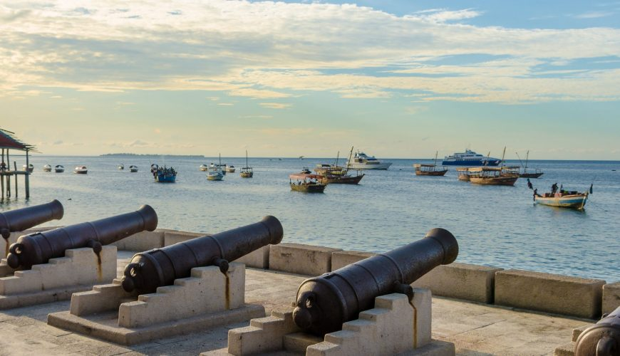 Five cannons lined up on the waterfront in Stone Town Zanzibar. Many fishing boats are out in the blue sea. It's a nice summer evening day with a few clouds in the sky and calm ocean