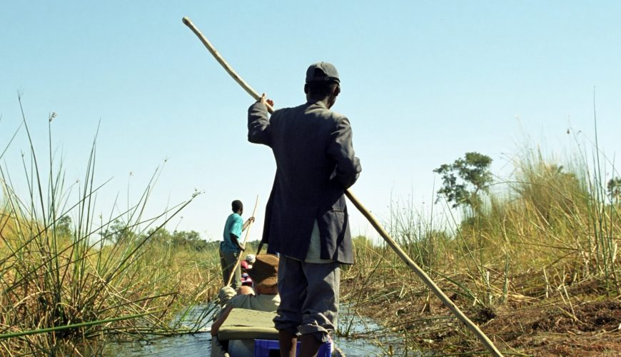 OKAVANGO DELTA, BOTSWANA - MAY 25 Mokoro man on 25 May 2002 at Botswana. Local people use wooden mokoros to transport tourists in the Okavango Delta
